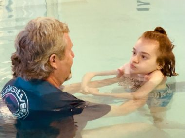 Jackie's daughter, Cammy, swims in the pool with YMCA aquatic director Scott Thurston.