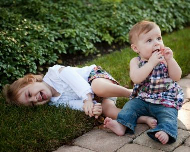 Symptoms / Rett Syndrome News / Photo of Cammy lying down, and Ryan sitting next to her.