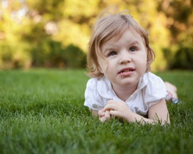 Symptoms / Rett Syndrome News / Photo of Cammy lying in the grass.