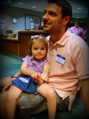 Natural History Study / Rett Syndrome News / Bill holds Cammy in his lap in the waiting room of the clinic.